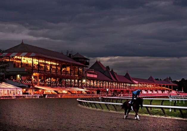 A horse works in the early morning light Thursday morning Aug. 27, 2015 at the Saratoga Race Course in Saratoga Springs, N.Y.   The clubhouse is illuminated by the tote boards in the infield and the night lights in the structure. (Skip Dickstein/Times Union) Photo: SKIP DICKSTEIN