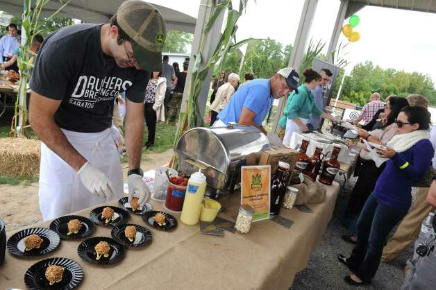 Sous chef Justin Nahow, left, of Druther's puts together a corn appetizer during the ?We?re All Ears Cornival,? a corn-themed chefs? competition to raise money for the Regional Food Bank of Northeastern New York at SEFCU?s outer parking lot on Thursday, Aug. 27, 2015, in Albany, N.Y. (Michael P. Farrell/Times Union) Photo: Michael P. Farrell / 00033144A