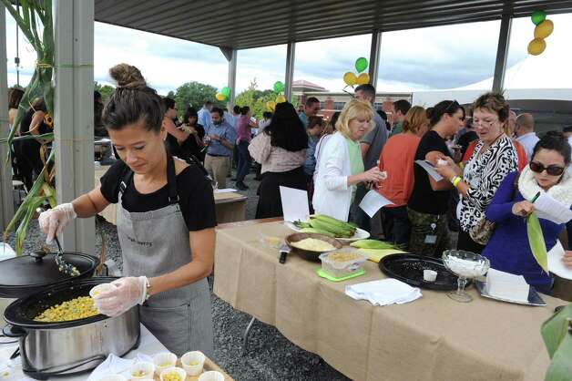 """Chef Mary Kenney, left, of Legal Pantry puts together a corn appetizer during the """"We're All Ears Cornival,"""" a corn-themed chefs' competition to raise money for the Regional Food Bank of Northeastern New York at SEFCU's outer parking lot on Thursday Aug. 27, 2015 in Albany, N.Y. (Michael P. Farrell/Times Union) Photo: Michael P. Farrell / 00033144A"""