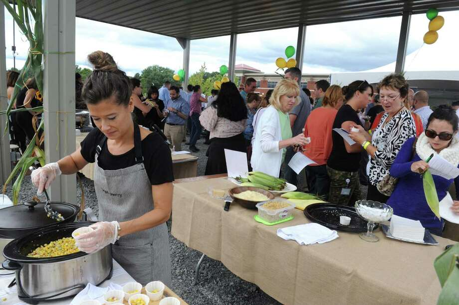 "Chef Mary Kenney, left, of Legal Pantry puts together a corn appetizer during the ""We're All Ears Cornival,"" a corn-themed chefs' competition to raise money for the Regional Food Bank of Northeastern New York at SEFCU's outer parking lot on Thursday Aug. 27, 2015 in Albany, N.Y. (Michael P. Farrell/Times Union) Photo: Michael P. Farrell / 00033144A"