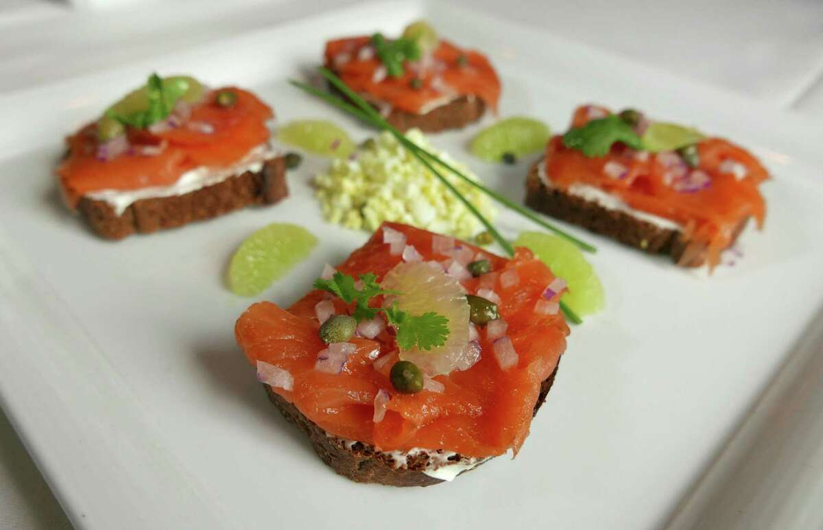 The plating of smoked salmon carpaccio at The Creek varies. Here, the thinly sliced fish tops slices of brown bread with cream cheese, and is topped with capers and diced red onions.