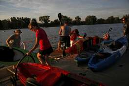 People unload at the end of a weekly sunset paddle hosted by Headwaters Kayak in Lodi, Calif., on Wednesday, August 19, 2015.