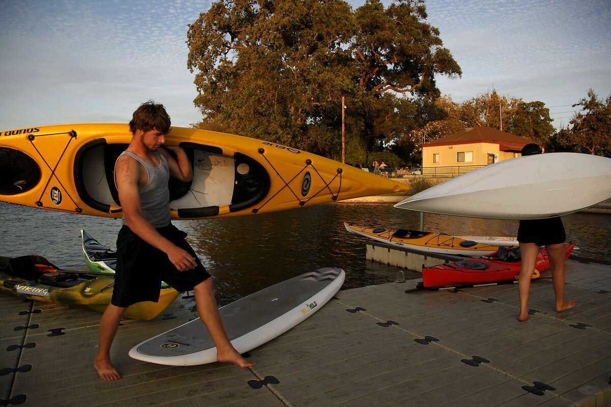 Eddy Stamp helps return boats at the end of a weekly sunset paddle hosted by Headwaters Kayak in Lodi, Calif., on Wednesday, August 19, 2015.