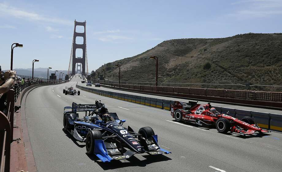 IndyCar drivers Josef Newgarden (67) and Graham Rahal (15) cross the Golden Gate Bridge in a motorcade paying tribute to Justin Wilson, Thursday, Aug. 27, 2015, in Sausalito, Calif. Wilson, of England, died Aug. 24 from injuries sustained at Pocono Raceway. The two-seat car in the background was driven by James Hinchcliffe carrying the Astor Cup trophy. The motorcade of IndyCars and safety vehicles delivered the trophy to Sonoma Raceway, the site of this weekend's championship-deciding Grand Prix of Sonoma. (AP Photo/Eric Risberg) Photo: Eric Risberg, Associated Press