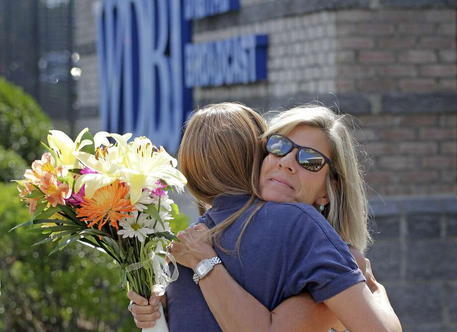 WDBJ employee Karen Loftus hugs Donna Anderson, whose daughter works at the station that employed the victims. Photo: Jay Paul, Getty Images