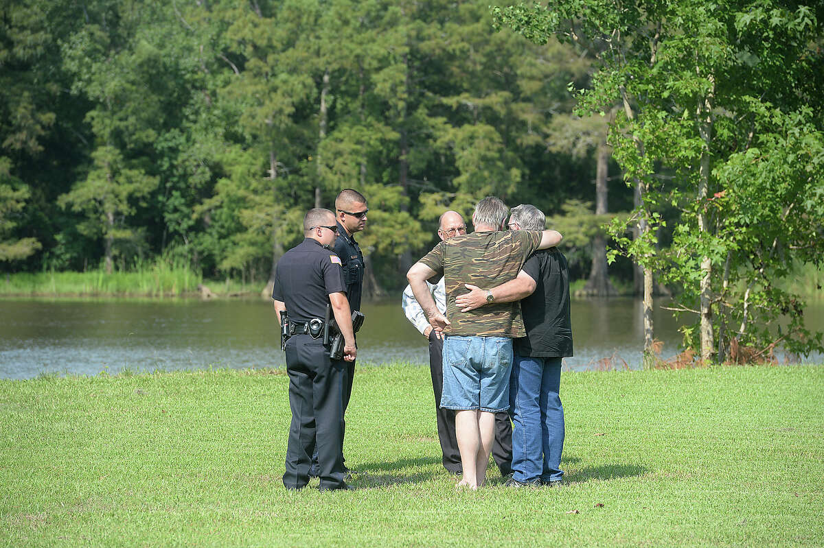 The husband of a woman presumed drowned is comforted as he talks with responders while emergency crews continue to search the Neches River near Collier's Ferry Park Thursday. The woman and her husband were swimming when she went under and failed to resurface, according to Beaumont Fire Department Captain Brad Penisson. Divers and search boats worked their way along the shoreline as recovery efforts continued throughout the afternoon. Photo taken Thursday, August 27, 2015 Kim Brent/The Enterprise