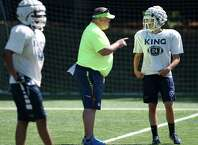 Head coach Danny Gouin talks to his players during football practice at King School in Stamford, Conn. Thursday, Aug. 27, 2015.