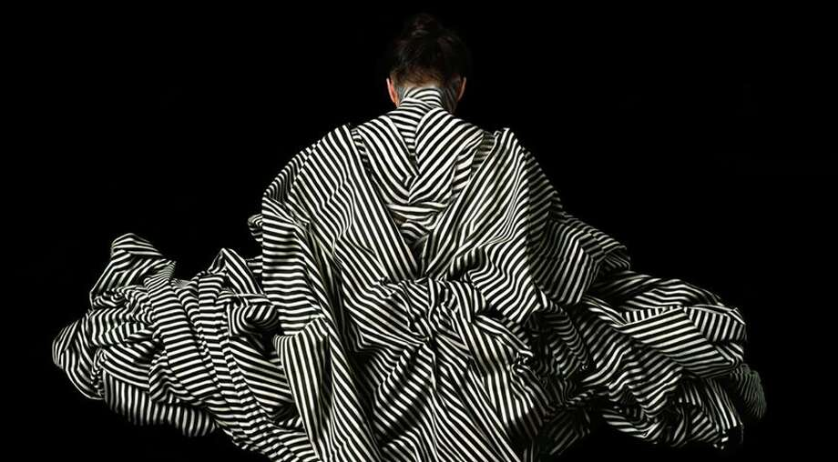 """La Dorsal"" is one of the photo performances by Cecilia Paredes that the artist refers to as having a ""silent"" background. The black and white stripes of kimono-like garment — and the title of the piece — allude to a geologic feature shared by Peru and Chile, neighboring countries with a long history of conflict. Photo: /"