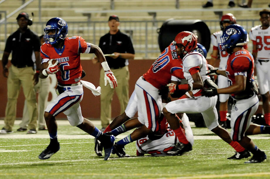 West Brook Bruin Innis Gaines, 6, dodges several tackles for a nice gain after an interception against the North Shore Mustangs at the Carroll Thomas Stadium September 26, 2014. Photo by Drew Loker. Photo: Drew Loker / ©2014. www.DrewLoker.com
