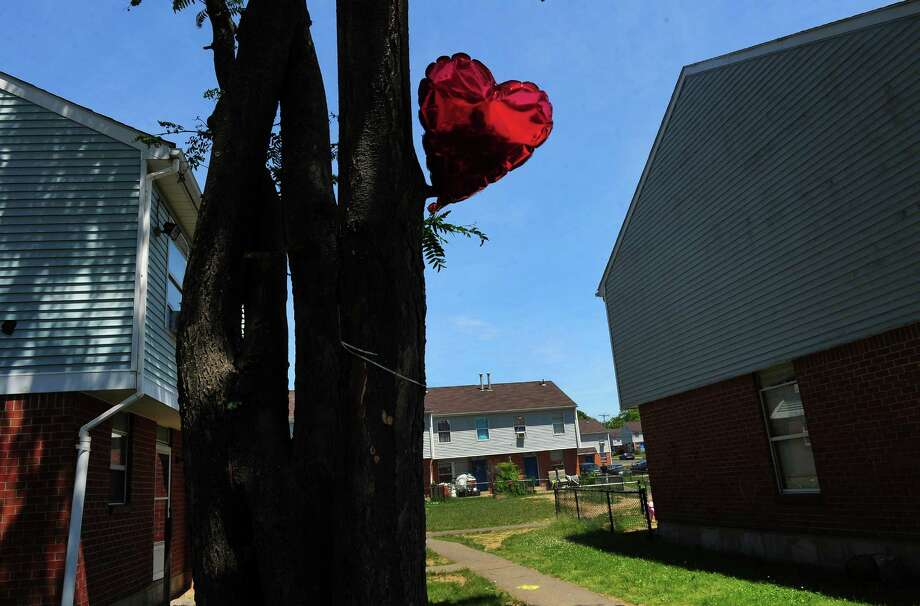 A single red balloon is tied to a tree in honor of a man who was shot and killed this past Thursday at the Trumbull Gardens housing complex on Trumbull Avenue in Bridgeport, Conn., on Saturday June 13, 2015. Seven other were injured in the incident. Photo: Christian Abraham / Hearst Connecticut Media / Connecticut Post