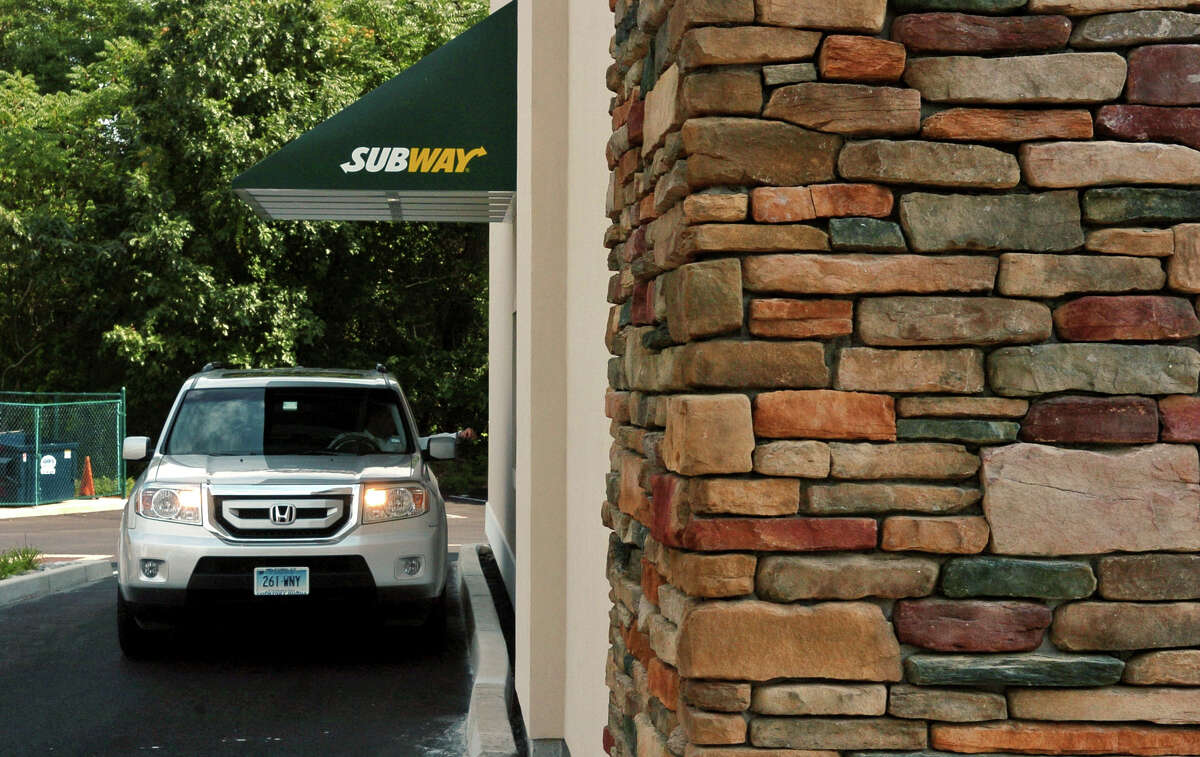 A car goes through the drive thru at the Subway along Post Road in Orange.