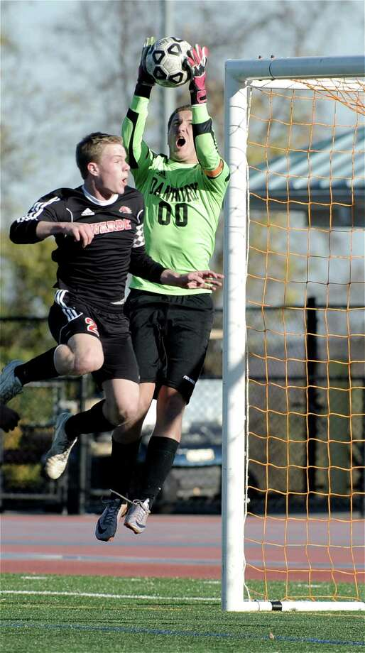 Danbury goalkeeper Ian Shannon (00) grabs the ball over Fairfield Warde's Brendan King (22) during a first round game in the  boys soccer Class LL State Tournament, between Fairfield Warde and Danbury high schools, played at Danbury High School, Danbury, Conn, on Monday, November 3, 2014. Photo: H John Voorhees III / H John Voorhees III / The News-Times