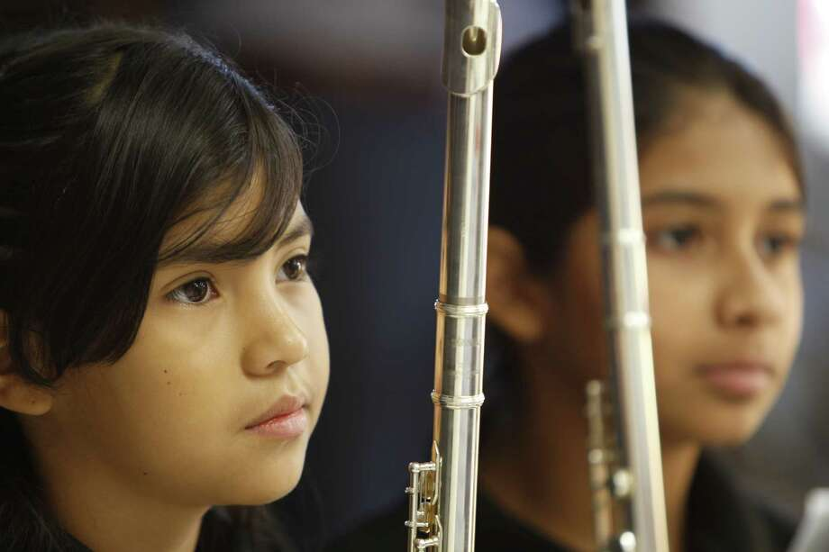 Whittier Elementary School 4th grader Marifer Lopez (left) and 5th grader Roxana Millan prepare to play their solos Thursday, Aug. 27, 2015, in Houston. The pair performed during a press conference announcing partnership between Washington's Kennedy Center, HISD and City of Houston in national arts education program. Houston is 19th city selected to join the program. Photo: Steve Gonzales, Houston Chronicle / © 2015 Houston Chronicle