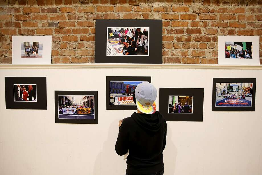 "A woman looks over photographs in the ""Define Undocumented: Flip the Script"" exhibition at the Women's Building in San Francisco. Photo: Connor Radnovich, The Chronicle"