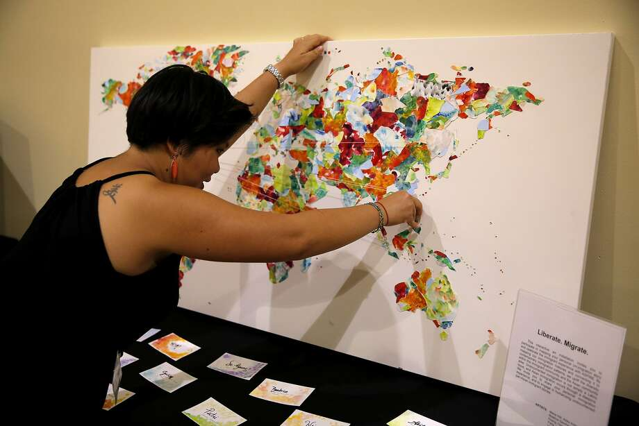 Hong Mei Pang pins a piece of thread to a map displaying where people have emigrated from at a show highlighting the experiences of undocumented pan-Asian youth at The Women's Building in San Francisco, California, on Wednesday, Aug. 26, 2015. Photo: Connor Radnovich, The Chronicle