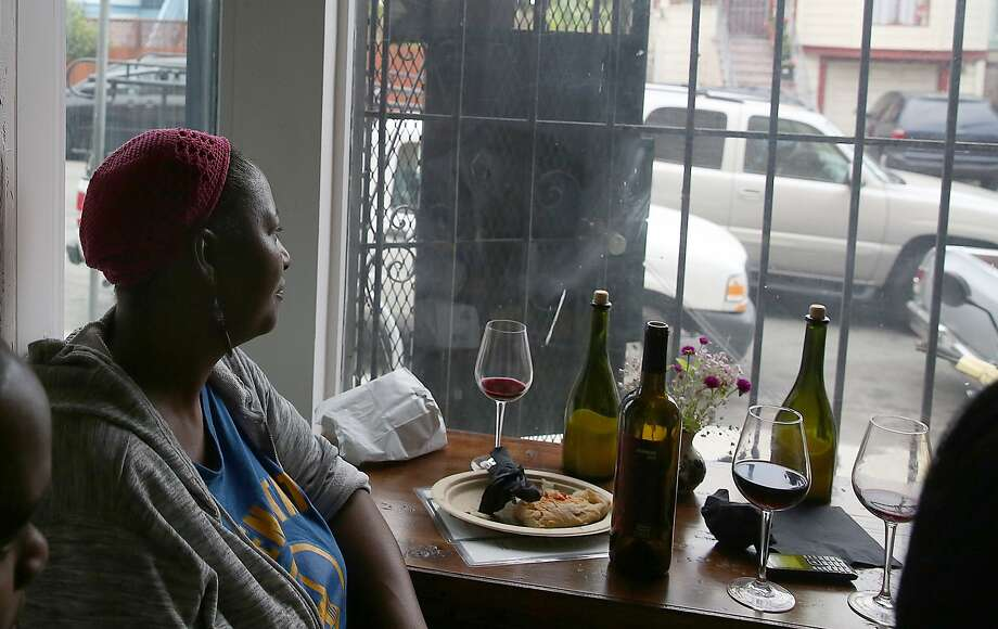 Debbie Payne looks out the window while dining with her daughters at Butchertown Gourmet in the Bayview-Hunters Point neighborhood of S.F. during Pizza and Wine night at the restaurant. Photo: Liz Hafalia, The Chronicle
