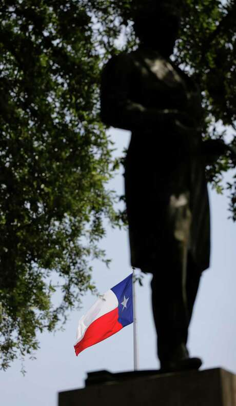 The Texas flag whips in the wind behind a statue of Confederate President Jefferson Davis on the University of Texas campus, Thursday, Aug. 27, 2015, in Austin, Texas. University of Texas officials are asking an Austin judge to let them move the century-old statue from central campus, but the Sons of Confederate Veterans, which says it seeks to celebrate Southern heritage, wants Davis to stay where it is. (AP Photo/Eric Gay) Photo: Eric Gay, STF / Associated Press / AP