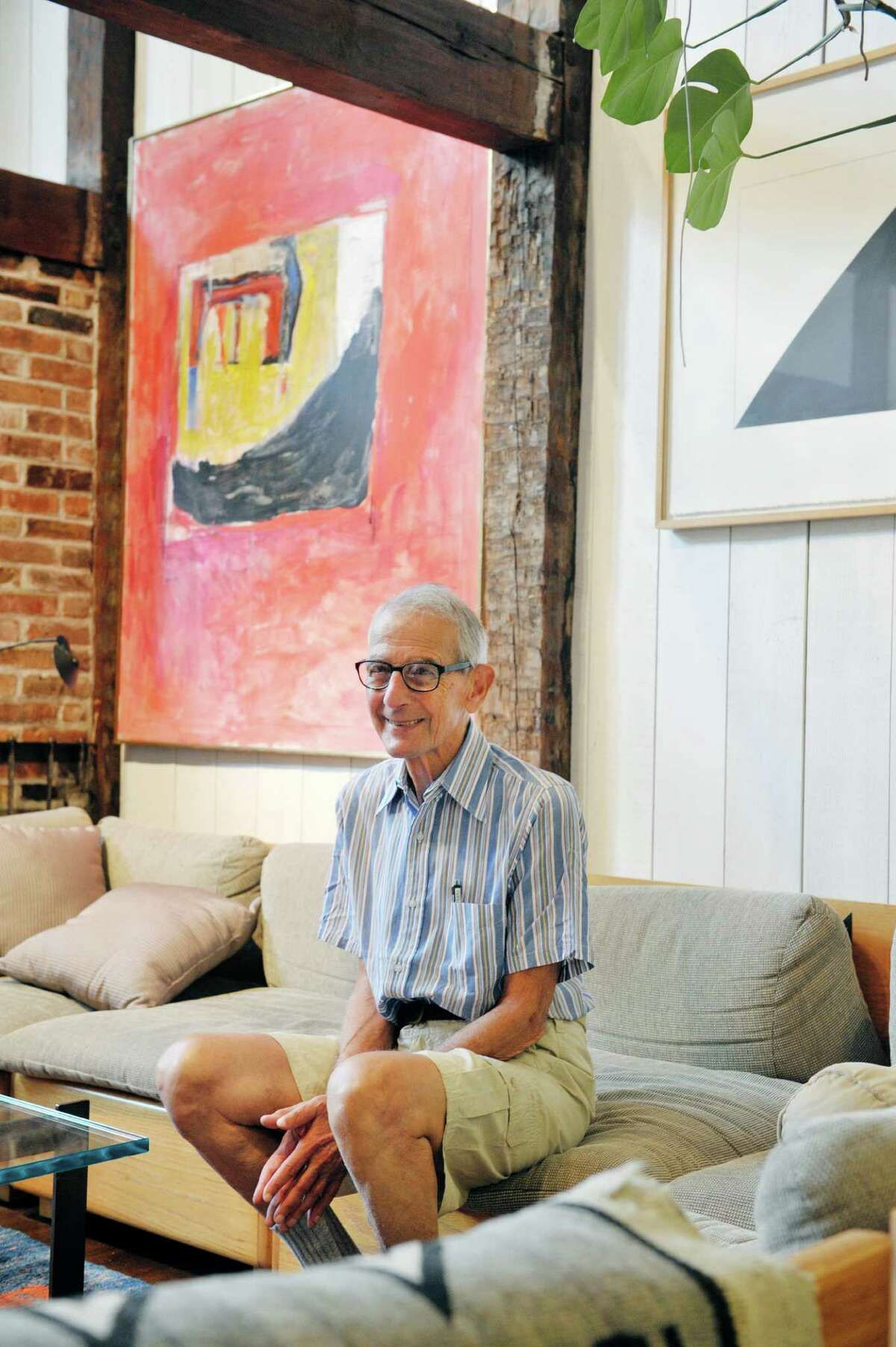 Werner Feibes, a retired architect, at his home on Tuesday, Aug. 25, 2015, in Schenectady, N.Y. In the background on the left is a painting by Paul Burlin, entitled Series of Nine #7, and on the right is a collage by Ellsworth Kelly entitled Slow Curve. (Paul Buckowski / Times Union)