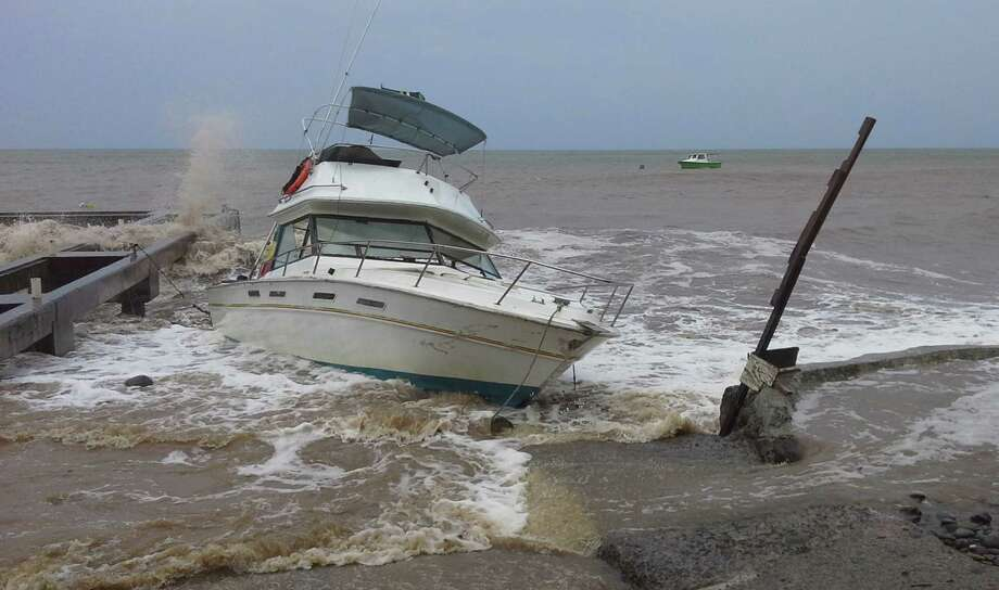 A boat sits in shallow water as Tropical Storm Erika passes through New Town, Dominica, Thursday, Aug. 27, 2015. Erika was expected to move near Puerto Rico and the Virgin Islands on Thursday and be near or just north of the Dominican Republic on Friday as it heads toward Florida early next week, possibly as a hurricane. (AP Photo/Carlisle Jno Baptiste) Photo: Carlisle Jno Baptiste, STR / AP