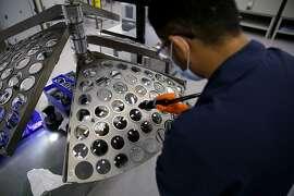Coating technician Harbinder Singh prepares a rack of lenses for a chemical treatment at VSP Global CEO Jim McGrann at the VSPOne Optical Technology Center in Sacramento, California, on Thursday, Aug. 27, 2015.