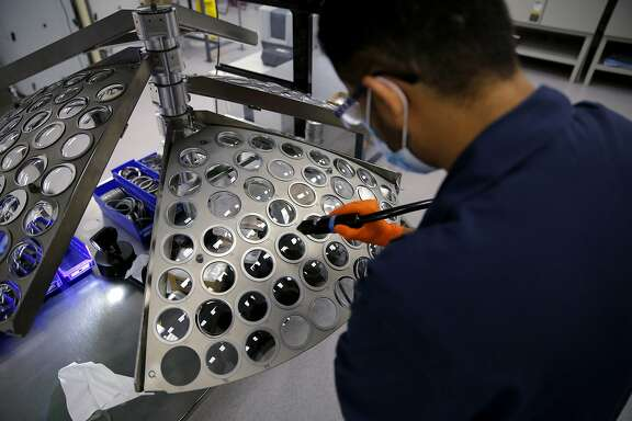 Coating technician Harbinder Singh prepares a rack of lenses for a chemical treatment at VSP Global CEO Jim McGrann at the VSPOne Optical Technology Center in Sacramento, California, on Thursday, Aug. 27, 2015.
