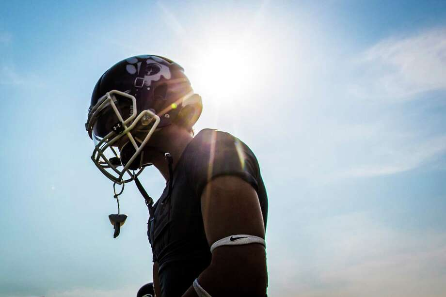 The sun shines against the helmet of a Kemper High School football players during warm ups before the game against Sam Rayburn, Thursday, Aug. 27, 2015, in Sugar Land. Photo: Marie D. De Jesus, Houston Chronicle / © 2015 Houston Chronicle