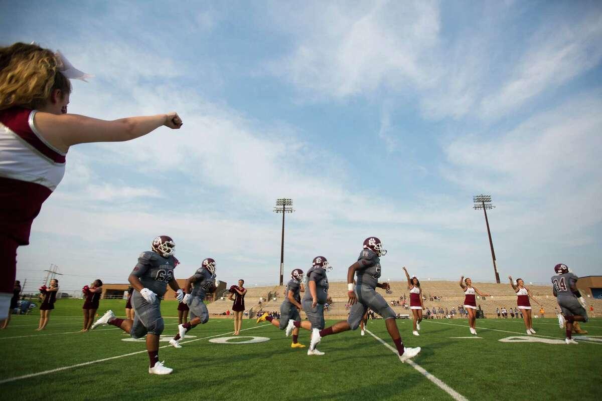 Kemper High School football players run onto the field, Aug. 27 in Sugar Land.