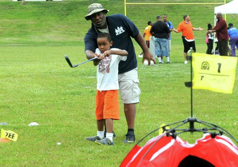 Chris Holloway helps six-year-old Haywood Watson with his golf stroke as part of the End-of-Summer City of Albany Department of Recreation's Allympics Event at Lincoln Park on Thursday Aug. 27, 2015 in Greenwich, N.Y. (Michael P. Farrell/Times Union) Photo: Michael P. Farrell / 00033105A