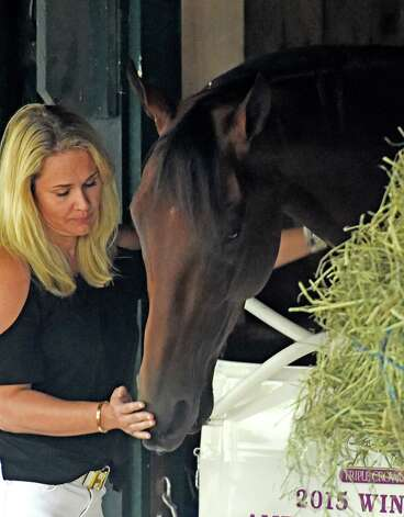 Jill Baffert enjoys a quiet moment with American Pharoah outside his stall Thursday evening Aug. 27, 2015 in the barn area of the Saratoga Race Course in Saratoga Springs, N.Y.    (Skip Dickstein/Times Union) Photo: SKIP DICKSTEIN
