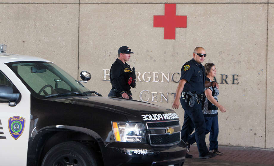 A woman is escorted at St. Joseph's Medical Center on Thursday after an off-duty officer wounded a combative patient. Photo: Cody Duty, Staff / © 2015 Houston Chronicle