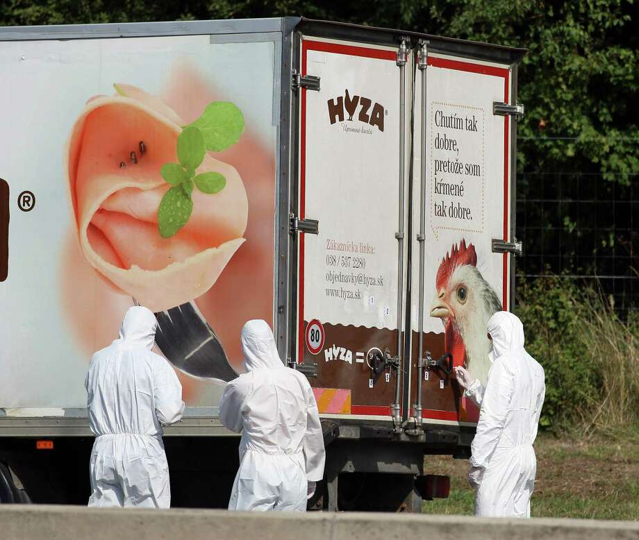 Investigators stand near a  truck that  stands on the shoulder of the highway A4 near Parndorf south of Vienna, Austria, Thursday, Aug 27, 2015. At least 20 migrants were found dead in the truck parked on the Austrian highway leading from the Hungarian border, police said. (AP Photo/Ronald Zak) Photo: Ronald Zak, STR / Associated Press / AP