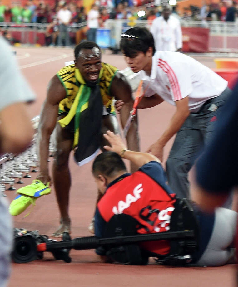 In this photo released by Xinhua News Agency, Jamaica's Usain Bolt gets up after he is rammed by a cameraman on a segway as he celebrates after winning the gold in the men's 200m final at the World Athletics Championships at the Bird's Nest stadium in Beijing, Thursday, Aug. 27, 2015. (Yue Yuewei/Xinhua via AP) NO SALES CHINA OUT ORG XMIT: XIN201 Photo: Yue Yuewei / Xinhua