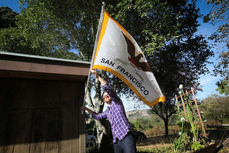 Roman Mars, host and creator of design radio show 99% Invisible, takes down the San Francisco flag outside of his house in Kensington, California on August 27, 2015. Mars has a campaign to change San Francisco's flag as he feels it's no longer representative of the city. He also believes that flags should not have writing on them since they are two sided and thus often read backwards. Photo: Gabrielle Lurie, The Chronicle