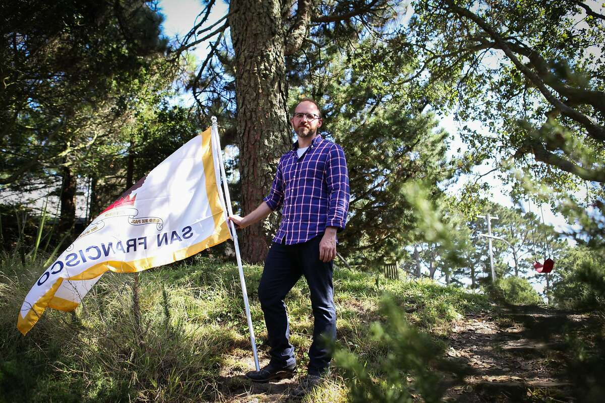 Roman Mars, host and creator of design radio show 99% Invisible, stands outside his home with the San Francisco flag in Kensington, California on August 27, 2015. Mars has a campaign to change San Francisco's flag as he feels it's no longer representative of the city. He also believes that flags should not have writing on them since they are two sided and thus often read backwards.