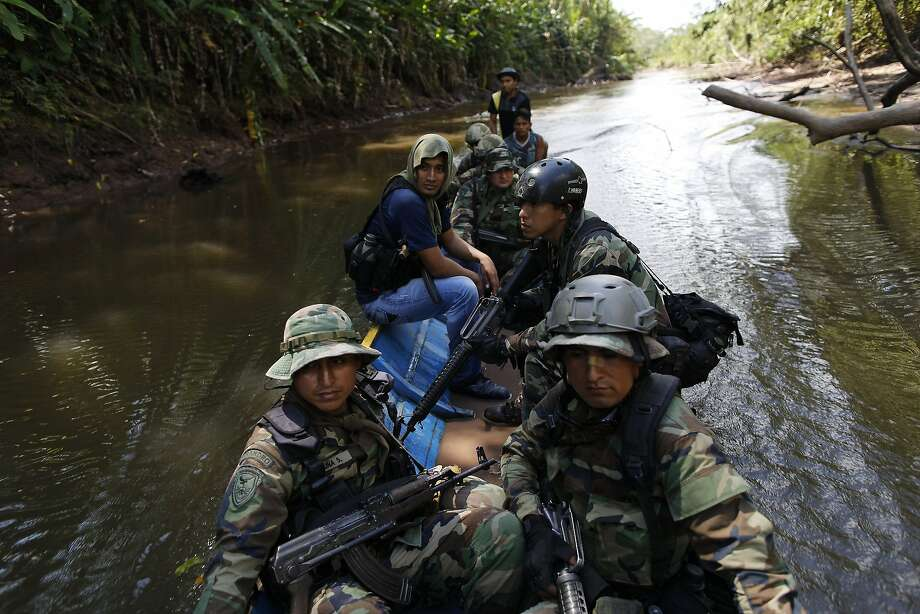 In this July 28, 2015 photo, counternarcotics special forces cross the Palcazu river as they head to crater a clandestine airstrip used by drug dealers in the Peruvian jungle near Ciudad Constitucion, Peru. The officers armed with assault rifles slowly negotiated rutted, muddy roads, walked for hours and forded streams to get to their destination. Photo: Rodrigo Abd, Associated Press