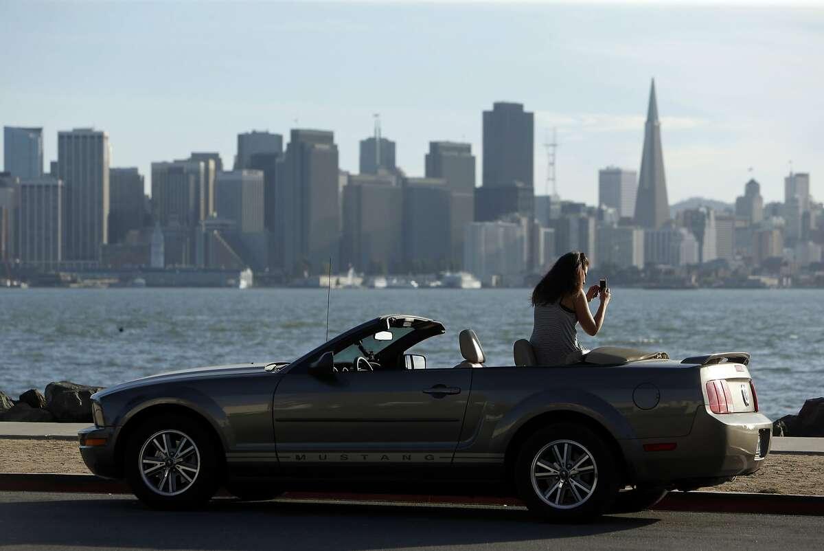 German tourist Sarah Hernandez takes a photo on Treasure Island in San Francisco, Calif., on Thursday, Aug. 27, 2015.