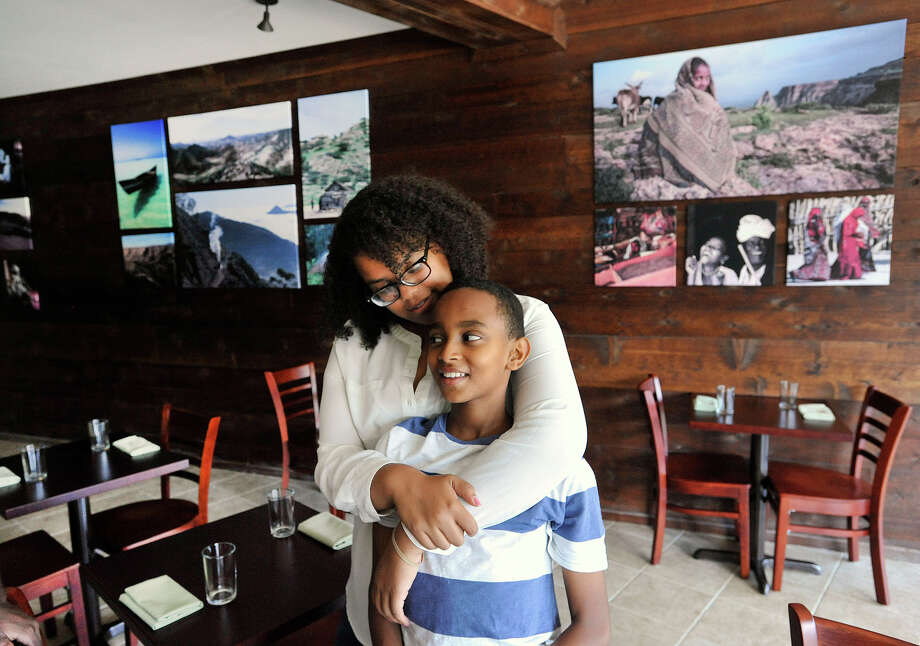 Elsa Mekonen embraces her cousin, Afewerki Tesfagabr, in the dining area of Teff, an Ethiopian and Eritrean restaurant, in Stamford, Conn., on Wednesday, Aug. 19, 2015. The restaurant is one of only a few African-American-owned restaurants in Stamford. Teff recently opened its doors on July 30. Photo: Jason Rearick / Hearst Connecticut Media / Stamford Advocate