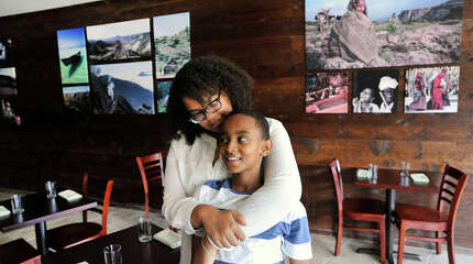 Elsa Mekonen embraces her cousin, Afewerki Tesfagabr, in the dining area of Teff, an Ethiopian and Eritrean restaurant, in Stamford, Conn., on Wednesday, Aug. 19, 2015. The restaurant is one of only a few African-American-owned restaurants in Stamford. Teff recently opened its doors on July 30.