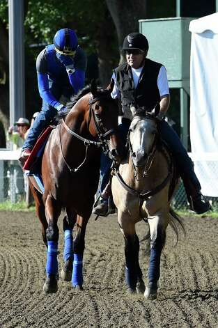 Triple Crown winner American Pharoah, left with exercise rider Georgie Alvarez aboard jogs around the track before beginning his gallop Friday morning Aug. 28, 2015 at the Saratoga Race Course in Saratoga Springs, N.Y.  Assistant trainer Jimmy Barnes is aboard Smokey the lead pony, right.  (Skip Dickstein/Times Union) Photo: SKIP DICKSTEIN