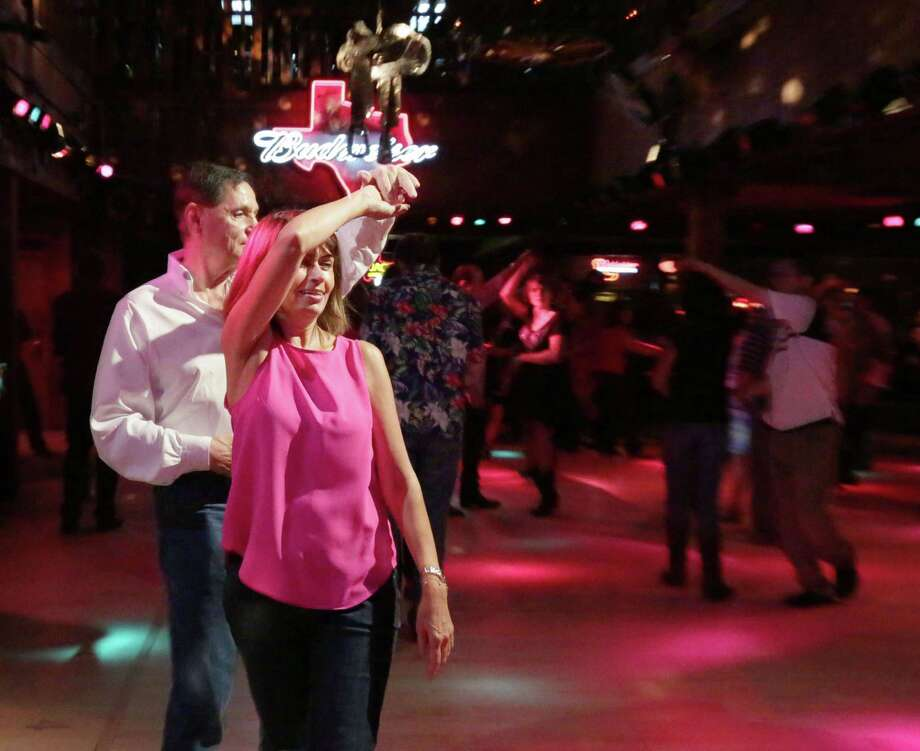 """Paul Blevins, left, and Sherry Tahanseb practice dancing at Wild West on Richmond Avenue Sunday, Aug. 23, 2015, in Houston. Blevins, an experienced dancer, has enjoyed teaching Tahanseb, who just started. """"I'm excited I'm learning,"""" Tahanseb said.  ( Jon Shapley / Houston Chronicle ) Photo: Jon Shapley, Staff / © 2015 Houston Chronicle"""