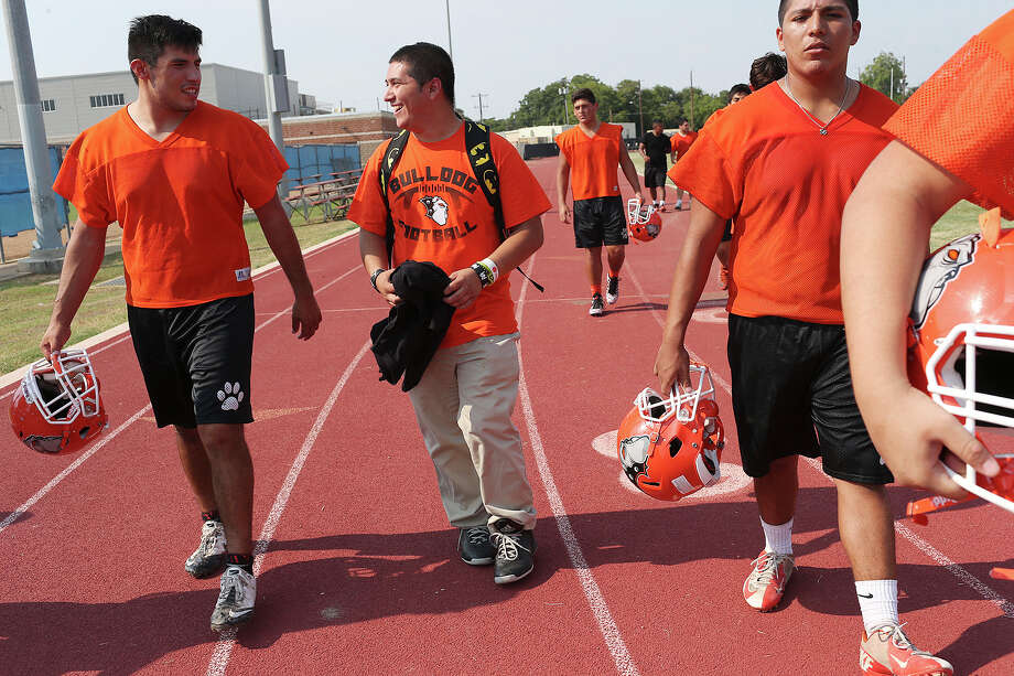 """Burbank High School senior and varsity football team manager Josh Evans, 19, center, walks off the practice field with team captain Jason Segovia, 18, left, Thursday, August 27, 2015. Evans, who is autistic, has been on the varsity football team for four years. He's not a player but the special needs student travels with the team and does everything but play football. """"I like helping out the coaches and love all the players. They are like my brothers. I protect them and we got each other's backs,"""" said Evans. Although he said he loves football and played in middle school, he also expressed an interested in science and cooking. This week is the start of the high school varsity football season. Photo: JERRY LARA /San Antonio Express-News / © 2015 San Antonio Express-News"""
