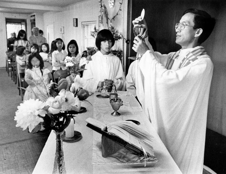 04/1980 - Father John Toan, who escaped from his native land in 1975, is one of seven Vietnamese priests in the Houston area, but Toan is the only one to have a totally Vietnamese congregation. At St. Peter's Catholic Church, his church in Kemah, Toan says Mass for some of the 50 children who attend his religious instruction class each Thursday. Photo: John Everett, © Houston Chronicle / Houston Chronicle