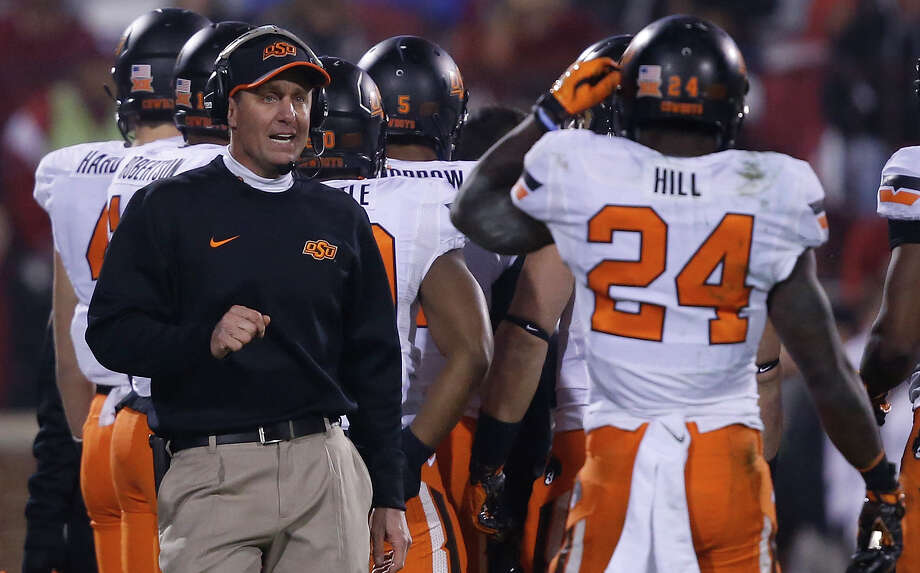 Oklahoma State head coach Mike Gundy talks to wide receiver Tyreek Hill (24) during a time out in the fourth quarter of an NCAA college football game against Oklahoma in Norman, Okla., Saturday, Dec. 6, 2014. Oklahoma State won 38-35 in overtime. Photo: Sue Ogrocki /Associated Press / AP