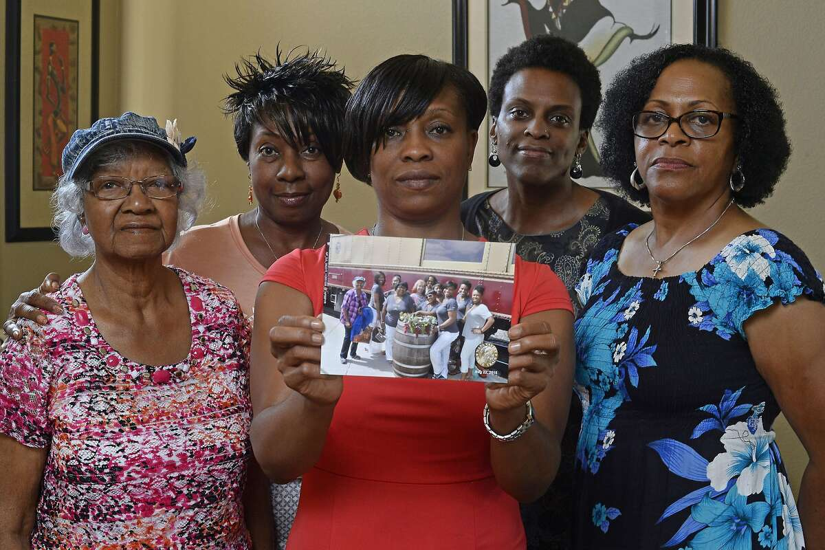 Five members of the Sistahs on the Reading Edge book club, all of Antioch, from left, Katherine Neal, Georgia Lewis, Lisa Renee Johnson, Allisa Carr and Sandra Jamerson stand together at Johnson's home in Antioch, Calif., on Monday, Aug. 24, 2015. The five women were among 11 African-American women who were were booted off the Napa Valley Wine Train on Saturday afternoon. Johnson holds a photograph of the group that was taken before boarding the train. (Jose Carlos Fajardo/Bay Area News Group via AP)