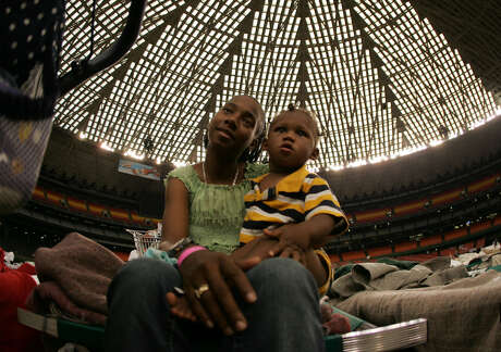 Keoka Lewis of New Orleans holds her son, Zwon, while they rest on a cot in the Astrodome.