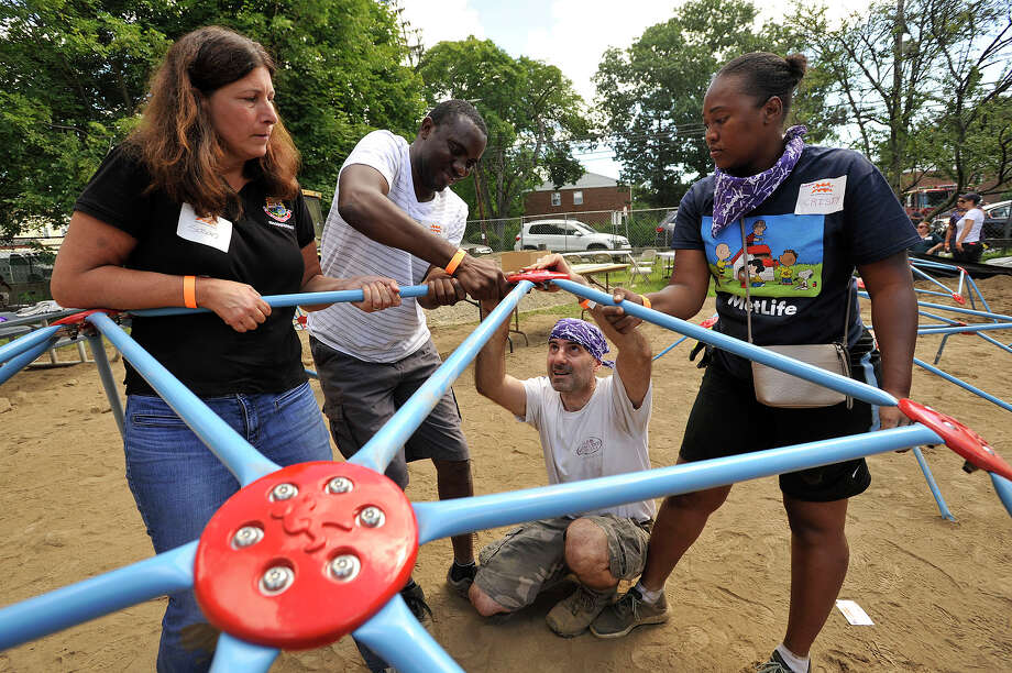 From left: Susan Kisken, an engineer with the city; Frantzca Telima, a resident of the neighborhood; Ralph DiCostanzo; and Christie Metellus, a resident of the neighborhood, work to assemble a jungle gym during a community effort to build a new playground at McKeithen Park in Stamford, Conn., on Friday, Aug. 28, 2015. Numerous volunteers from MetLife, Barnum Financial Group, the City of Stamford, Charter Oak Communities, Family Centers, KaBOOM!, and residents from Stamford's East Side neighborhood helped in the project. The design of the playground is based off of children's drawings. Photo: Jason Rearick / Hearst Connecticut Media / Stamford Advocate