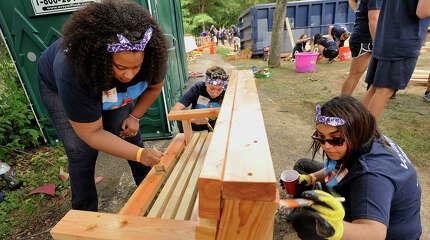 Kahlilah Lilley, left, Mia Morris, center, and Asma Manzoor work to stain a bench during a community effort to build a new playground at McKeithen Park in Stamford, Conn., on Friday, Aug. 28, 2015. Numerous volunteers from MetLife, Barnum Financial Group, the City of Stamford, Charter Oak Communities, Family Centers, KaBOOM!, and residents from Stamford's East Side neighborhood helped in the project. The design of the playground is based off of children's drawings.
