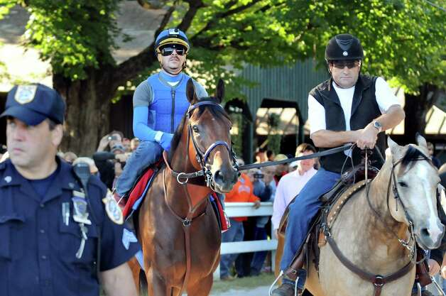 Triple Crown winner American Pharoah, center, is escorted to the racetrack for a morning workout with stablemate Smokey and assistant trainer Jim Barnes, right, on Friday, Aug. 28, 2015, at Saratoga Race Course in Saratoga Springs, N.Y. American Pharoah will compete in Saturday's Travers Stakes. (Cindy Schultz / Times Union) Photo: Cindy Schultz