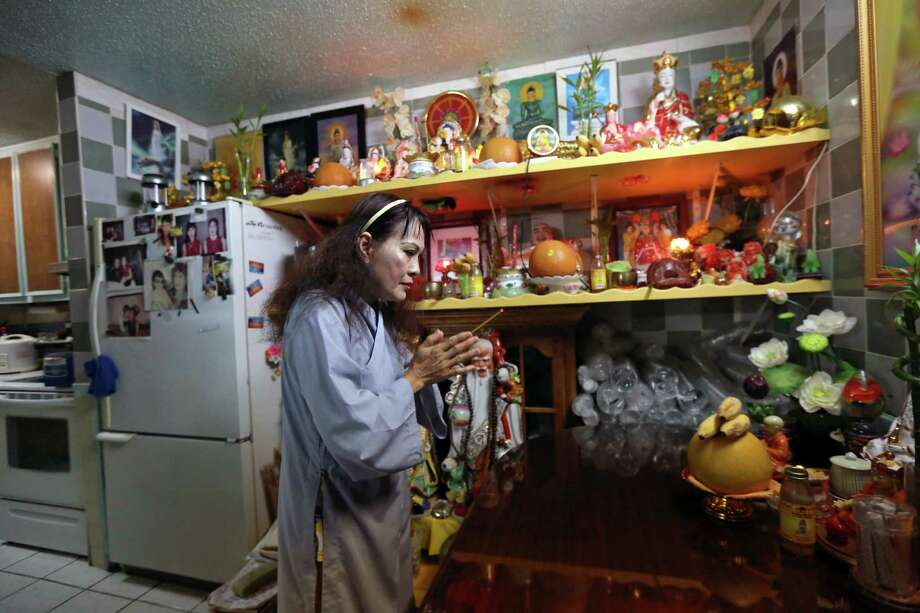 Hien Thi Tran makes an offering to Buddha at a shrine in her home at the Thai Xuan Village, August 1, 2015. Photo: Gary Coronado, Houston Chronicle / © 2015 Houston Chronicle