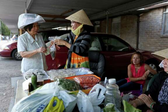 Hien Thi Tran, right, a resident of the village, sells confections in the parking lot at the Thai Xuan Village, August 2, 2015.